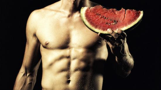 Muscular man holding watermelon